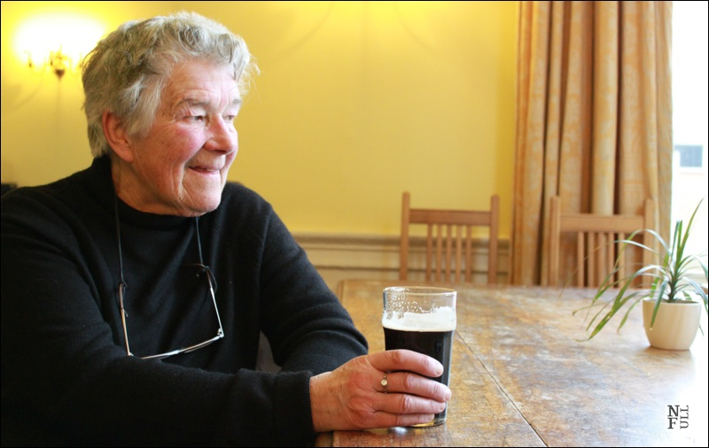 Dervla Murphy drinking a pint of guiness in the Royal Geographical Society