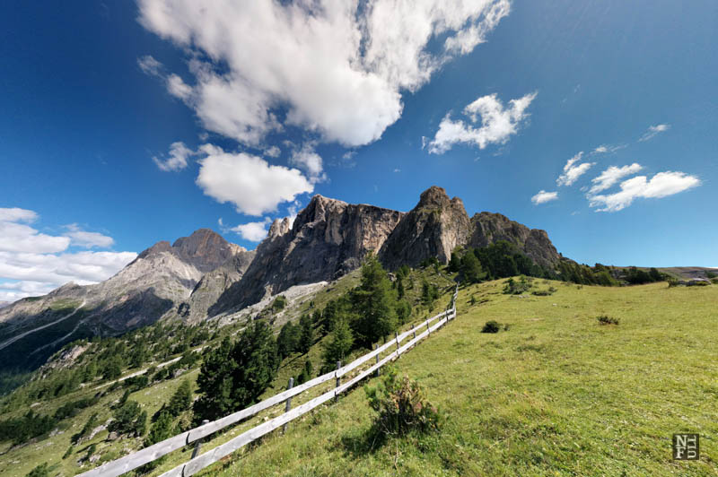 Blue sky and green meadow, the Dolomites, Italy.